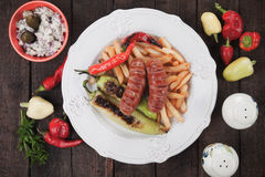 Grilled sausages and french fries Royalty Free Stock Photos