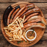 Grilled sausages with french fries. Junk food. Oktoberfest traditional menu, German food. Tasty grilled sausages with crispy french fries and sauce, top view Royalty Free Stock Photo