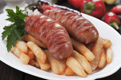 Grilled sausages with french fries Royalty Free Stock Images