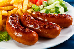 Grilled sausages and French fries Stock Images