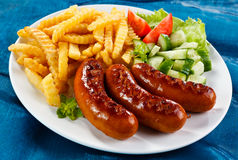 Grilled sausages and French fries Royalty Free Stock Image