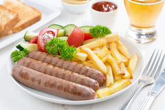 Grilled sausages with French fries and vegetables Royalty Free Stock Photos
