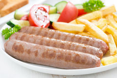 Grilled sausages with French fries and vegetables, close-up Royalty Free Stock Photos