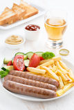 Grilled sausages with French fries, vegetables and glass of beer Stock Image