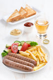 Grilled sausages with French fries, vegetables and glass of beer Stock Images