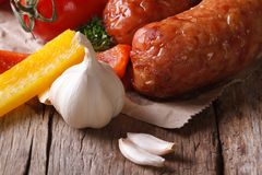 Grilled sausages and fresh vegetables close up on an old table Stock Image