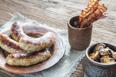 Grilled sausages with fried bacon rashers and mushrooms Royalty Free Stock Image