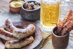 Grilled sausages with fried bacon rashers and mushrooms Royalty Free Stock Photography