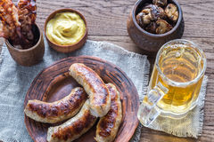 Grilled sausages with fried bacon rashers and mushrooms Stock Photos