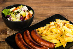Grilled sausages and fried potatoes on the black plate on the rustic surface. Grilled sausages and fried potatoes on the black plate on the rustic wooden Stock Photography