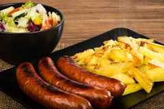 Grilled sausages and fried potatoes on the black plate on the rustic wooden surface. Grilled sausages and fried potatoes on the black plate on the rustic Stock Images