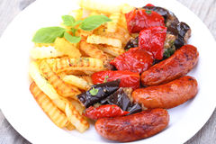 Grilled sausages and fried potatoes Royalty Free Stock Photography