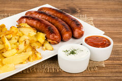 Grilled sausages and fried potatoes on the white plate on the rustic surface. Grilled sausages and fried potatoes on the white plate on the rustic wooden Stock Photos