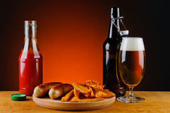 Grilled sausages, fries and beer Royalty Free Stock Photography