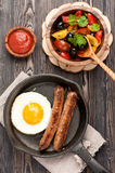 Grilled sausages in a frying pan and fried egg Royalty Free Stock Photos