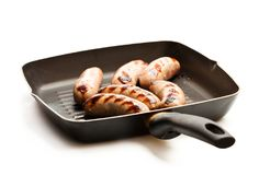 Grilled  sausages in a  frying pan isolated on white. Grilled  sausages in a frying pan isolated on white Stock Photo