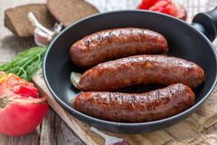 Grilled sausages in frying pan and a ripe tomato. Stock Photo