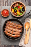 Grilled sausages in a frying pan, and vegetable salad Stock Photos