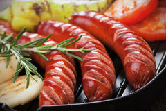 Grilled sausages. Grilled german sausages and vegetables in grilling pan Stock Image