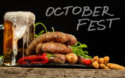 Grilled sausages with a glass of beer on a wooden table. Rustic style. Snacks for the Oktoberfest stock image