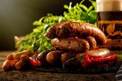 Grilled sausages with a glass of beer on a wooden table Stock Photos