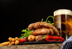 Grilled sausages with a glass of beer on a wooden table Royalty Free Stock Photo