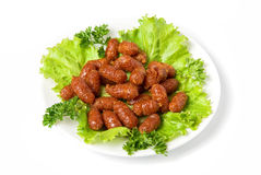 Grilled sausages on green lettuce Stock Images