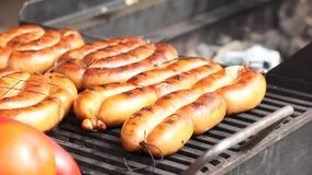 Grilled sausages on grills with tomatoes and sweet peppers stock video footage