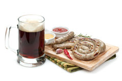Grilled sausages with ketchup, mustard and mug of beer Royalty Free Stock Photos