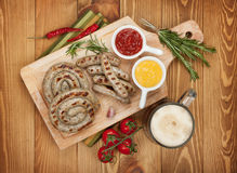 Grilled sausages with ketchup, mustard and mug of beer Stock Image