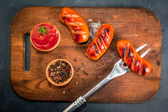 Grilled sausages with ketchup and spices Royalty Free Stock Images