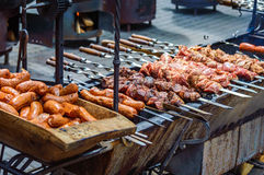 Grilled sausages and meat on skewers. Grill sausages in a wooden trough and meat on skewers. Ukrainian festive fairs Stock Images