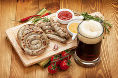 Grilled sausages with mug of beer Royalty Free Stock Photos