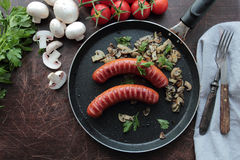 Grilled sausages with mushrooms Royalty Free Stock Photos