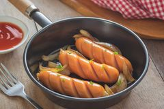 Grilled sausages with onion in frying pan Royalty Free Stock Photography