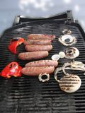 Grilled sausages, onion and peppers, ready to eat, Royalty Free Stock Image