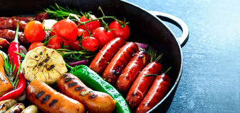 Grilled sausages in a pan royalty free stock photos