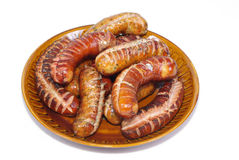 Grilled sausages on a plate. Grilled sausages on plate - isolated Royalty Free Stock Photography