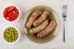Grilled sausages in plate, bowls with sweet pepper, green peas Stock Image