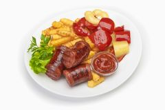 Grilled sausages with potatoes fries and sweet bulgarian peppers and red sauce ketchup.  Stock Image