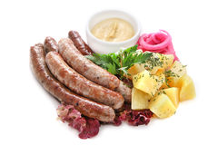 Grilled sausages with potatoes and gravy. Sausage with potatoes, onions, parsley, dill and sauce on a white background Stock Image