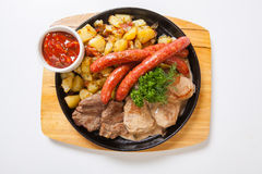 Grilled sausages with potatoes, and roasted meat on a grill pan royalty free stock image