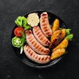 Grilled sausages with potatoes and vegetables on a black stone background. Meat. Top view. Free copy space stock photos