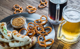 Grilled sausages with pretzels and mugs of beer Stock Images