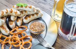 Grilled sausages with pretzels and mugs of beer Royalty Free Stock Photos