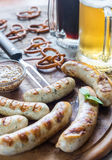 Grilled sausages with pretzels and mugs of beer Royalty Free Stock Photography