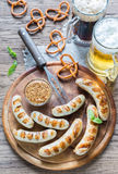 Grilled sausages with pretzels and mugs of beer Stock Photos
