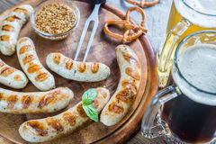Grilled sausages with pretzels and mugs of beer Royalty Free Stock Images