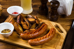 Grilled sausages with roast potato with spices Royalty Free Stock Photography