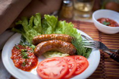 Grilled sausages with salad and tomatoes. Grilled sausages with salad, tomatoes and ketchup Royalty Free Stock Photos